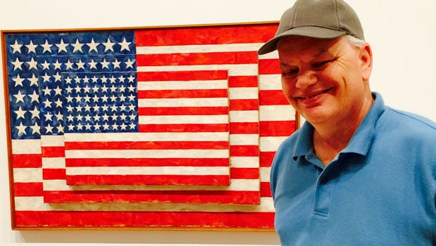 Steve Lomazow in front Jasper Johns' painting at The New Whitney.